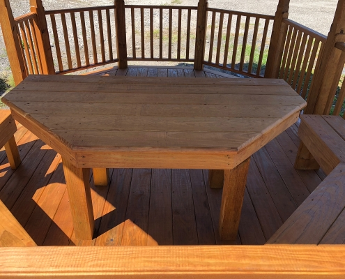 Half round table with benched seating inside a gazebo