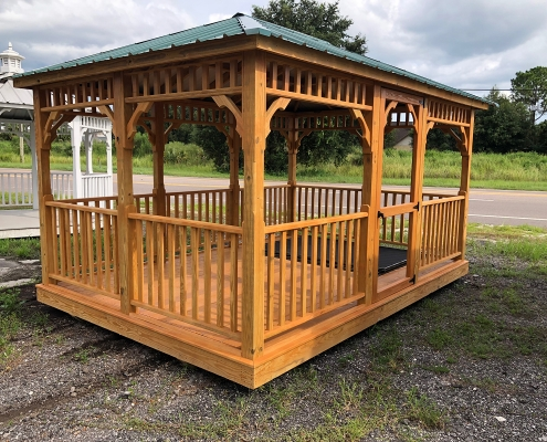 Light brown wood gazebo with green tin roof