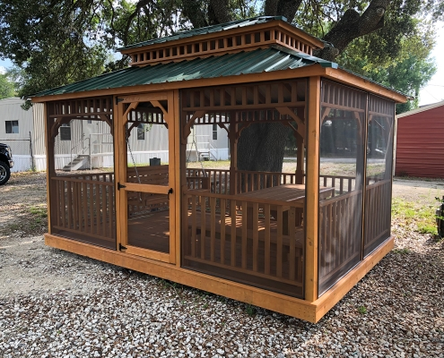 Light wood gazebo with shade screen and green tin roof