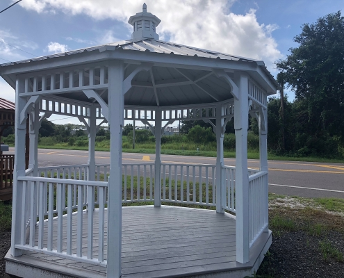 Opening view of a white wood gazebo with light grey tin roof
